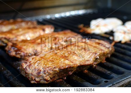 Juicy beef sirloin steaks on barbecue grill. Focus on foreground.