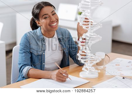Future of genetic science. Happy nice female student sitting in front of the DNA model and taking notes while studying genetics