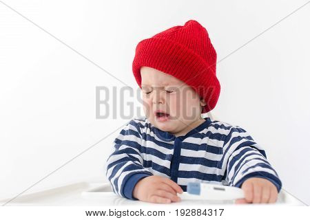 The baby sneezes sitting in a chair in a red hat and a vest with a thermometer in his hand, his eyes are closed