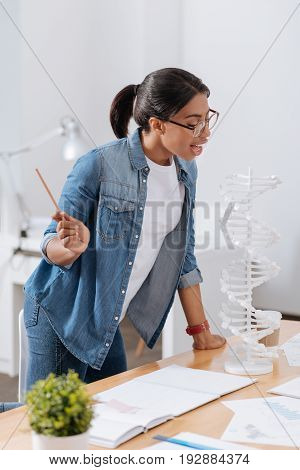 Scientific laboratory. Intelligent smart attractive woman standing near the table and holding a pencil while looking at the gene model