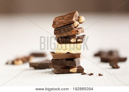 Broken chocolate pieces with nuts on table
