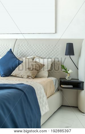 Light bed with multicolored pillows and coverlets on the white wall background. On the right there is a black shelf with a flower in a glass vase and a book, lamp. Closeup. Indoors. Vertical.