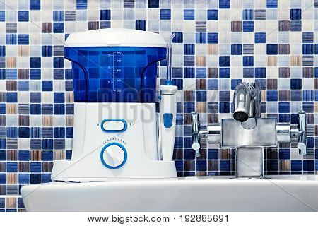 Oral Hygiene, Bathroom Objects Concept. Mouth Teeth Cleaning Irrigator Modern Tool On Sink.