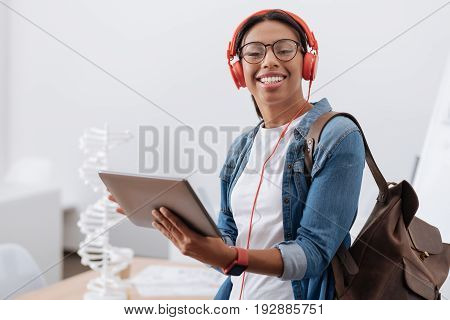 Age of technology. Happy cheerful nice student holding a tablet and wearing headphones while listening to music