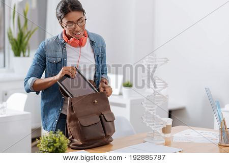 Packing things. Pleasant good looking young woman standing near the table and putting the tablet in her bag while packing her things