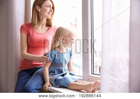 Mother and daughter sitting on sill near window poster