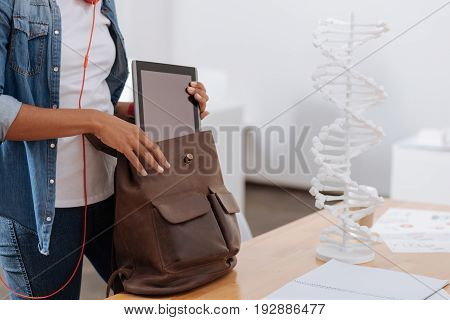 Portable device. Close up of a modern table being put into the bag by a nice good looking female student