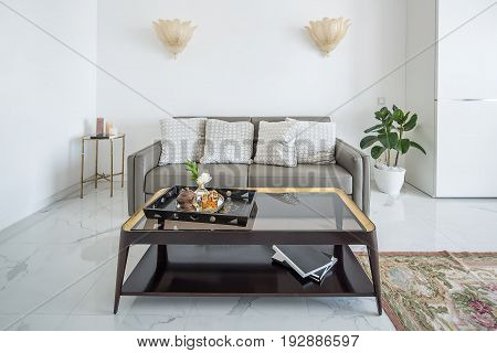 White modern interior with tiled floor with a carpet. There are fancy golden lamps on the wall, gray sofa with pillows, table with a glass tabletop with a tray, plants, small metal table with candles.