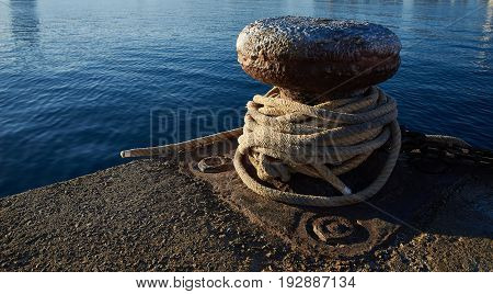 Rusty iron mooring bollard of a harbour with boat ropes.