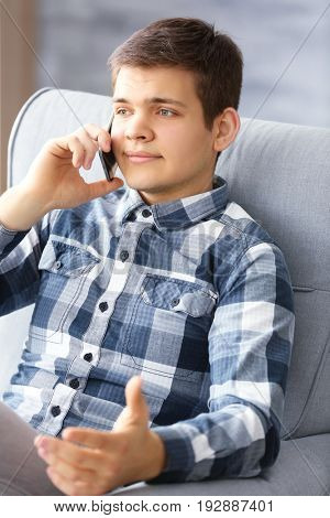 Handsome man talking on phone at home