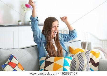 Beautiful woman watching TV at home