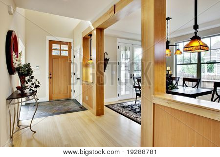 Wide view of home entrance and hallway with dining room in view
