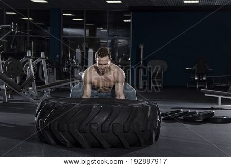 Muscular, Strong and fit man pushing tire in modern fitness center.Cross workout.Functional training