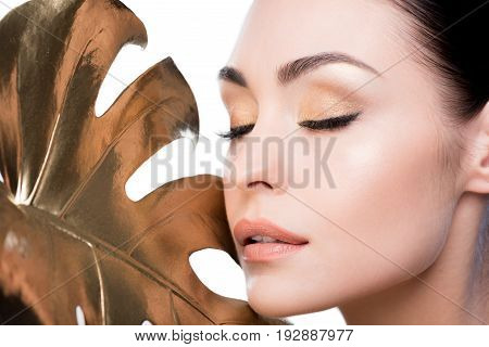 Headshot Of Woman With Big Golden Leaf Near Face Isolated On White