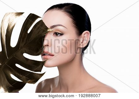Portrait Of Woman Covering Eye With Big Golden Leaf And Looking Away Isolated On White