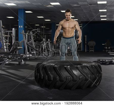 Muscular, Strong and fit man preparing to push tire in modern fitness center.Cross workout.Functional training