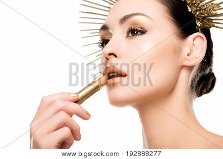 Glamorous Woman In Headpiece Applying Golden Lipstick Isolated On White