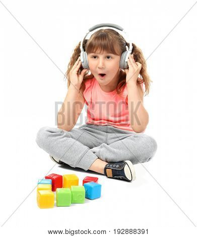 Cute funny girl with headphones and cubes on white background