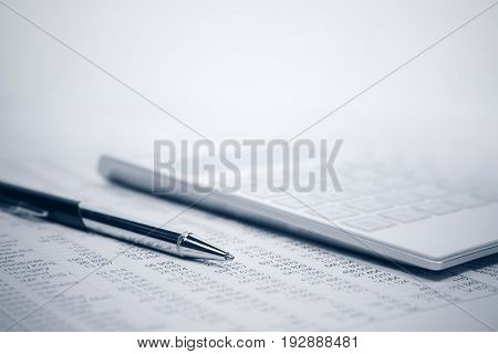 Financial accounting. Pen and calculator on business report