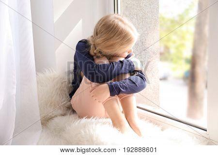 Cute sad girl sitting on window sill at home