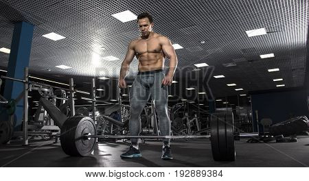 Attractive muscular shirtless athlete preparing to do deadlift in modern gym. Functional training. Start position