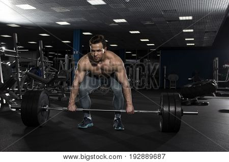 Attractive muscular shirtless athlete preparing to do heavy  deadlift exercise in modern gym. Functional training.Cross workout