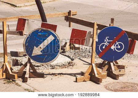 Road works and weather worn traffic signs detour and bicycles lane ends signage
