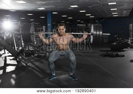 Attractive muscular shirtless athlete doing heavy  squat exercise in modern gym. Functional training.