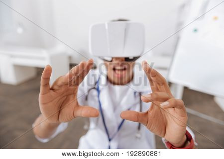 Virtual reality. Selective focus of doctors hands pressing on the virtual screen while being in the virtual reality