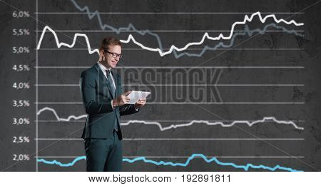 Businessman with smartphone standing on a diagram background. Business, finance, investment concept.