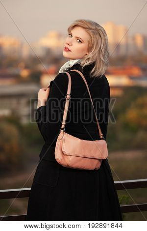 Blond woman with handbag walking in city street. Stylish fashion female model in black coat outdoor