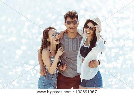 happy asian man hugging with two cheerful girls on riverside