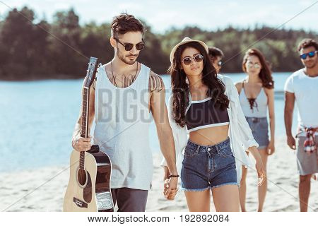happy interracial couple holding hands and spending time with their friends on beach