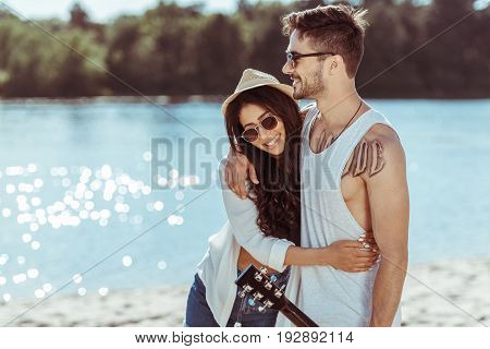 Young Smiling Interracial Couple In Sunglasses Embracing On Riverside