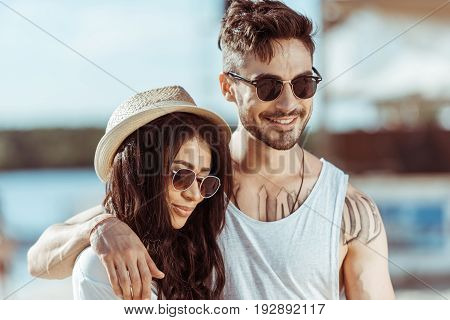 Happy Interracial Couple In Sunglasses Hugging And Spending Time Together