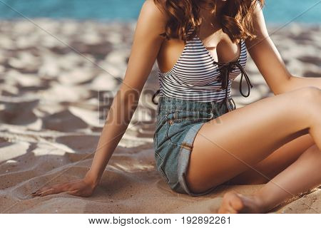 Cropped shot of slim young woman sitting on sand at beach