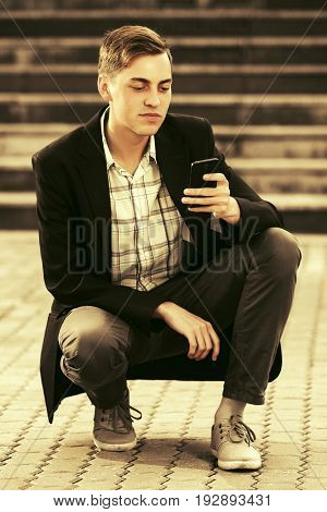 Young handsome business man using smart phone sitting in city street. Stylish trendy male model in black jacket