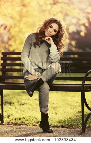 Happy young woman with long curly hairs sitting on bench in city park. Stylish fashion model in pullover and ripped jeans outdoor