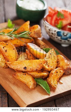 Spicy roasted potato wedges with herbs and tomato salad