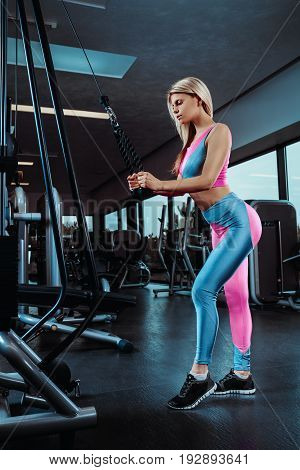 Young fitness woman execute exercise with exercise-machine in gym. Beautiful blonde in a sporty uniform