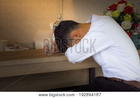Young man heartbroken in casual clothes is sleeping near the bottle of Vodka on a bar counter in pub