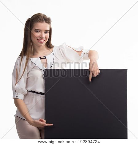 Young happy woman portrait of a confident businesswoman showing presentation, pointing placard black background. Ideal for banners, registration forms, presentation, landings, presenting concept..