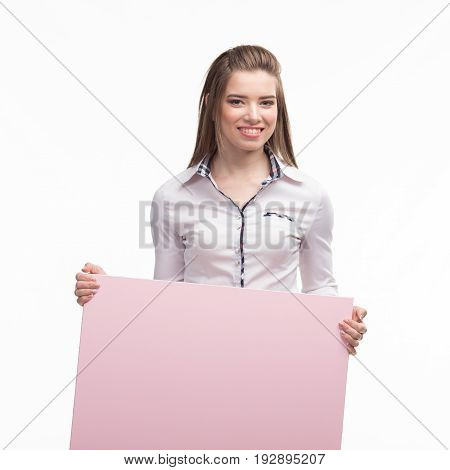 Young happy woman portrait of a confident businesswoman showing presentation, pointing placard pink background. Ideal for banners, registration forms, presentation, landings, presenting concept..