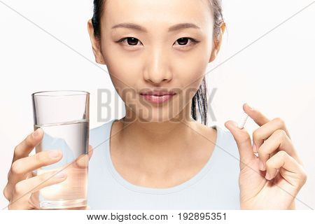 Pharmacy, pharmacy, woman on white isolated background holds a pill, capsule, asian.