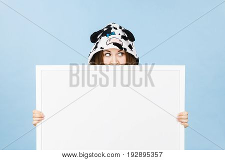 Teenage girl in funny nightclothes pajamas cartoon style covering her face with blank empty banner board. Advertisement copyspace.