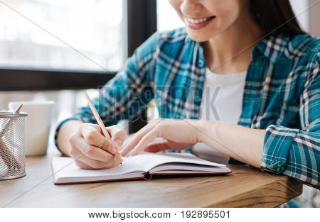 Remembering tips. Adorable charming motivated girl sitting in a public place and feeling inspired while noting down some of her thoughts