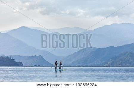 The young couple does new but popular sport of Standup paddleboarding (SUP - surfing) on the lake Pheva in the Himalayas against the background of the mountains thawing in a haze. March 3 2017. Nepal. Pokhara.