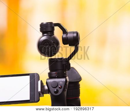 QUITO, ECUADOR- DECEMBER 22, 2017: Osmo Mobile gimbal, new generation of electronic stabilizer in a blurred forest background.