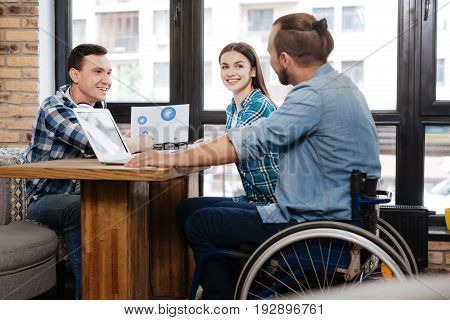 Positive prognosis. Quick witted intelligent helpful man showing his friends some data while discussing prospects of their startup in a cafe