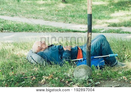 Old poor homeless man sleeping in the grass on the street. Illustrative editorial image. June - 25. 2017. Novi Sad, Serbia. Social documentary street.